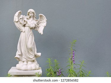 Beautiful angel statue against gray wall background.