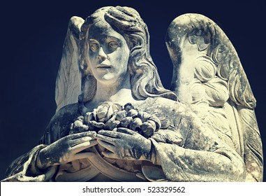Beautiful angel statue holding a rose and buds in its hands. From Antique Graveyard of Avola, close to the Baroque town of Noto, (Sicily).