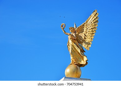 A beautiful angel statue on top of a pillar in outdoor space of Assumption University in Samuthprakarn province, Thailand