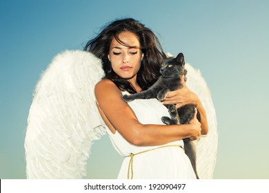 beautiful angel woman against sky with cat in her arms