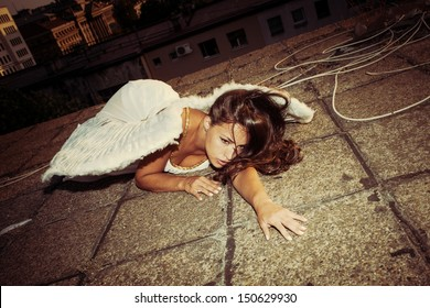 beautiful angel woman with white wings lie on roof