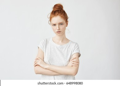 Beautiful angry ginger girl looking at camera with crossed arms.