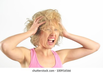 Beautiful angry girl pulling her messy hair on isolated background