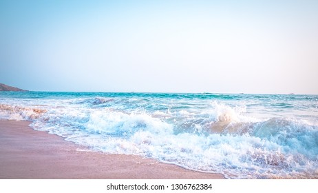 Beautiful Anjuna beach in the northern Goa, India. Popular beach vacations destination in Goa with blue Arabian Sea waves, rocks, and typical beach cafe.