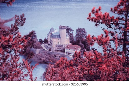 Beautiful Annecy lake (known as Europe's cleanest lake) with the castle seen through the pine trees. Haute-Savoie, France. Toned photo. Selective focus on the pine twigs.