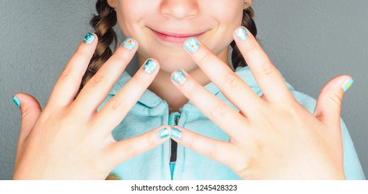 Beautiful anonymous young girl with creative manicure finger nail paint up close
