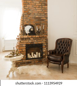 Beautiful antique  fireplace and leather armchair in interior