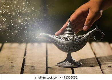 Beautiful antique metal lamp in true Aladin style, hand touching and animated star dust coming out, sitting on wooden surface