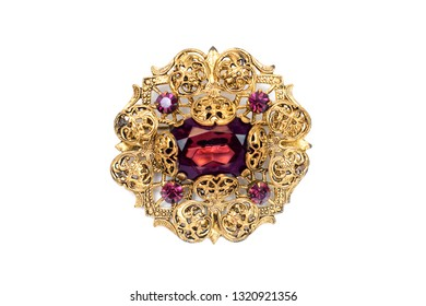 Beautiful antique precious brooch with openwork pattern and stone on white isolated background