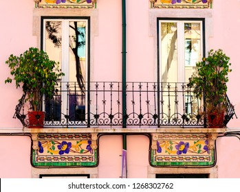 Beautiful antique windows of one of the houses in downtown of Lisbon, Portugal. Windows are ornated by gorgeous painted tiles in art nouveau style on the pink background.
