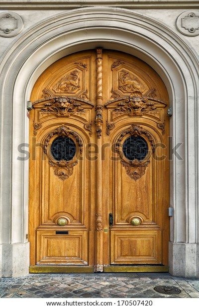 Beautiful antique wooden door in Paris. Lion heads and other elaborate carvings decorate the imposing arched double doors. Close up detail.