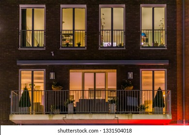 beautiful apartment balcony decorated with plants, lighted windows by night, Modern dutch architecture