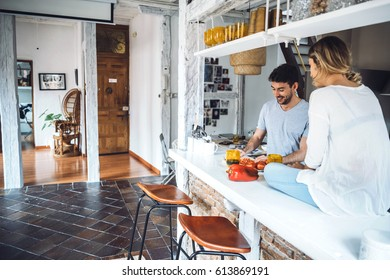 Beautiful apartment with two young people cooking at kitchen and talking.