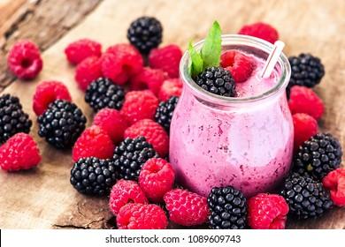 Beautiful appetizer pink raspberries, blackberry fruit smoothie or milk shake in glass jar with fresh berries background, top view. Yogurt cocktail. Close up. Natural detox. Liquid ice cream.