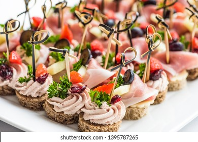 Beautiful appetizers on a table. Round base of the canape is carved from a wholegrain baguette and top is either duck liver pate or prosciutto ham and cheese. Decorated with fruits.