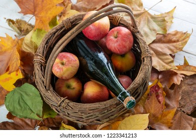 beautiful apples and a bottle of cider, on autumn leaves