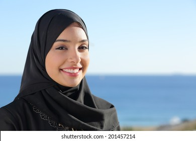 Beautiful arab saudi woman face posing on the beach with the sea in the background