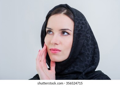 Beautiful arab woman looking up isolated on grey background