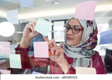 Beautiful Arab woman wearing hijab putting sticky notes on glass in modern office.