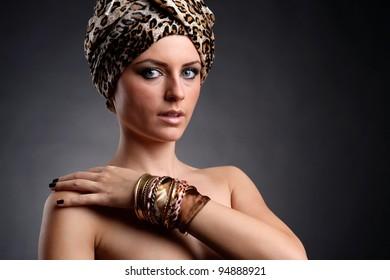 A beautiful arabian blonde woman posing in a studio wearing jewelry.