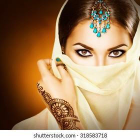Beautiful Arabian girl portrait. Young Hindu woman with mehndi tattoos from black henna on her hands. Portrait of beauty Indian model with bright make-up who hiding her face behind the veil