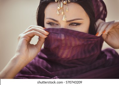 Beautiful Arabian woman portrait outdoors. Young Hindu woman. Portrait of beauty Indian model with bright make-up who hiding her face behind the veil standing over gold desert background.