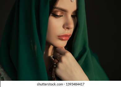 Beautiful Arabian woman portrait traditional costume indoors. Young Hindu woman. Close-up portrait of beauty model with bright makeup who hiding her face behind transparent veil standing over dark