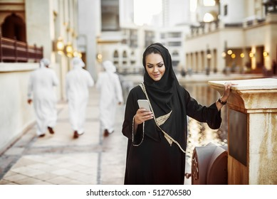 Beautiful Arabian woman typing on smartphone and smiling.