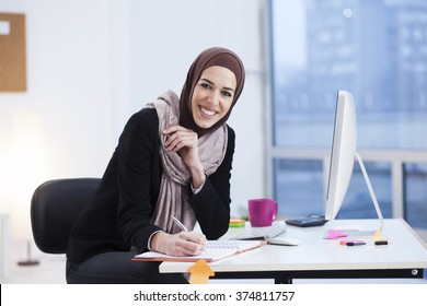 Beautiful Arabic business woman writes in a notebook in her office
