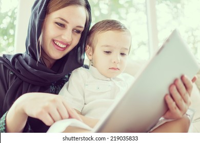Beautiful Arabic family, mother and cute baby with tablet