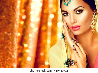 Beautiful Arabic girl portrait. Beauty young Arabian woman with menhdi, perfect make-up and accessories hiding her face behind a veil. Indian Bride. Arab Traditions and culture concept