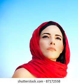 Beautiful arabic woman wearing red scarf, traditional muslim clothes, latest fashion design, stylish female portrait over blue natural background with copy space, soft focus