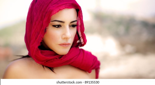 Beautiful Arabic woman wearing red scarf, stylish female portrait over soft natural background with copy space