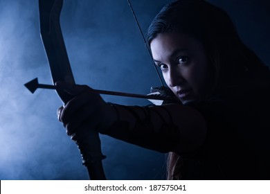 Beautiful archery woman aiming, smoky background