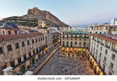 Beautiful architecture around an urban square in Alicante, Spain with an early morning view across to the castle of Santa Barbara