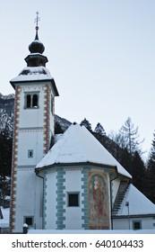 beautiful architecture of local church in snowy winter time, bohinj, slovenia