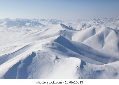 Beautiful Arctic aerial landscape. Top view of the snowy mountains and hills. Traveling and hiking in the far north of Russia. Location place: Meingypilgyn Range, Chukotka, Siberia, Russian Far East.