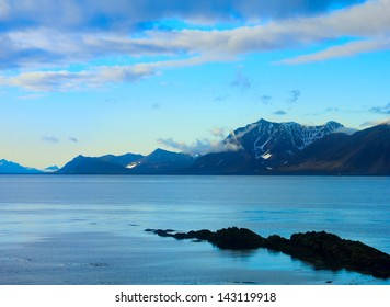 Beautiful arctic landscape with calm blue water of Greenland Sea and distant mountain range against the background of dramatic cloudy sky in Spitsbergen (Svalbard island) Norway