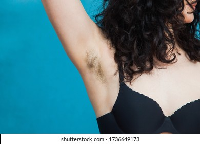Beautiful armpits with dark hair. Woman raising her arms and showing unshaved armpits. Bodypositive, feminism and bodycare concept.