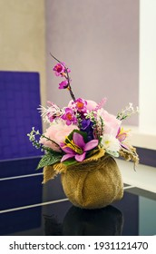 A beautiful arrangement of artificial flowers on the dining table. Vertical photography.