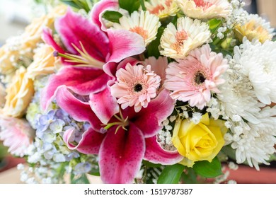 A beautiful arrangement of fresh flowers asters, baby's breath, chrysanthemums, roses and lily flowers as a foreground.