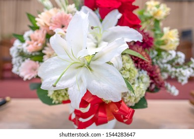 A beautiful arrangement of fresh flowers asters, baby's breath, chrysanthemums, lily, roses and  white casablanca flowers  as a foreground.