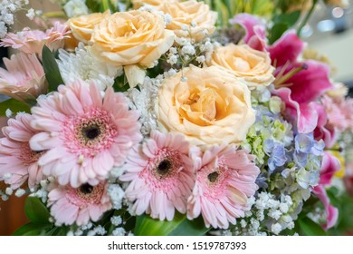 A beautiful arrangement of fresh flowers baby's breath, chrysanthemums, lily, aster and roses as a foreground.