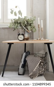 Beautiful arrangement with green plant branches candles and alarm clock on small table