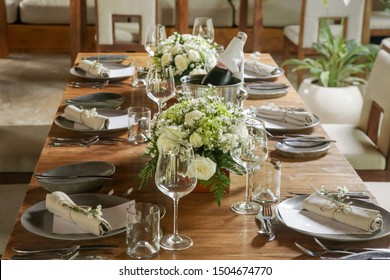 The beautiful arrangement on the wooden table, white roses and ceramic plates. Boho chic wedding table setting.