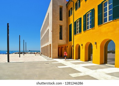 beautiful art colorful yellow facade of old architecture building and windows and columns in front of Bagno della Regina beach in Livorno Tuscany, Italy