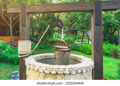 Beautiful artesian well made by stones and wheel pulley with metal bucket and rope in peaceful garden atmosphere. Retro stone water well in rural area. Garden decoration with antique items.