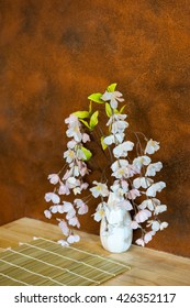 Beautiful artificial flowers and white ceramic vase on the wooden table.