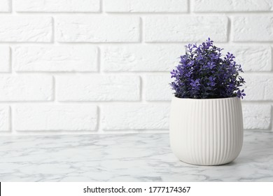 Beautiful artificial plant in flower pot on white marble table near brick wall. Space for text