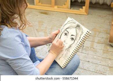 beautiful artist paints the portrait in the art Studio